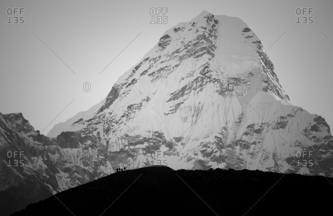 Hikers silhouetted against the mountain slopes of Ama Dablam (6812m), Sagarmartha National Park, Nepal (Black and white)