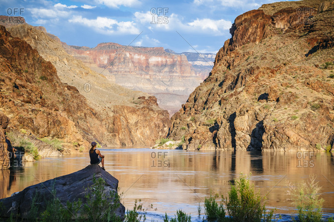 A woman sits by the Colorado River.