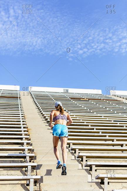 Woman running up steps in stadium