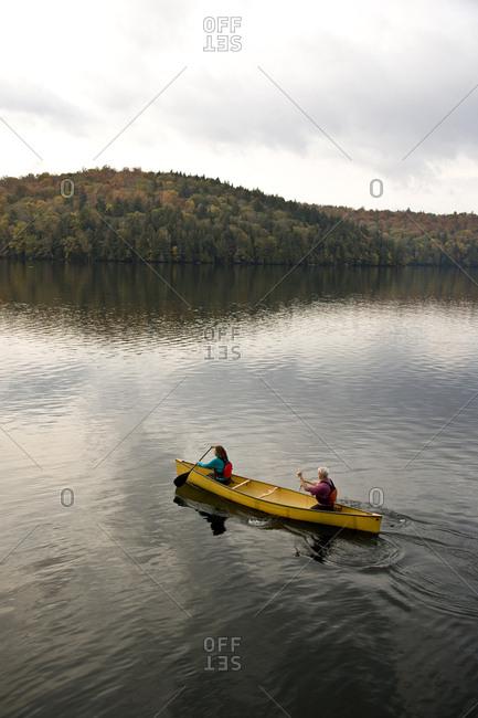 Young couple paddle  canoe  on Lake Placid in the Adirondacks, upstate New York, USA.