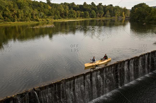 Two young men canoe above damn on Farmington River, Collinsville, Connecticut, USA.