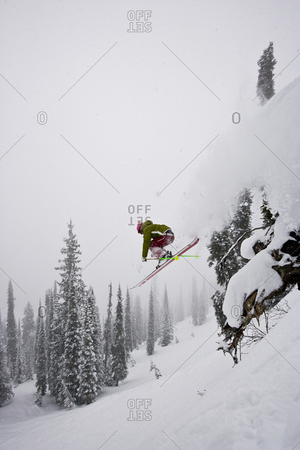 Young woman  catches air while skiing fresh powder during snowstorm at Island Lake Resort, Fernie, BC, Canada.
