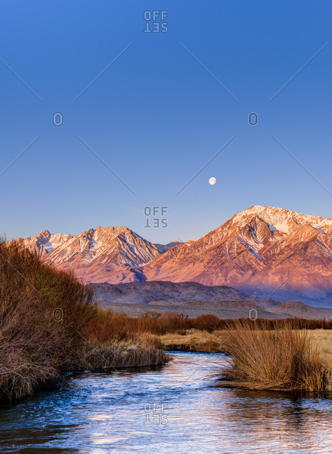 Full moon at sunrise over Eastern Sierra and Owens River