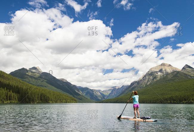 Woman Paddle boarding In Bowman Lake At Glacier National Park, USA