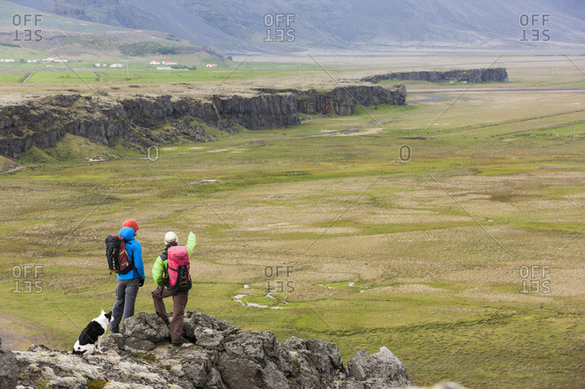 Two climbers overlooking a climbing cliffband. Iceland.