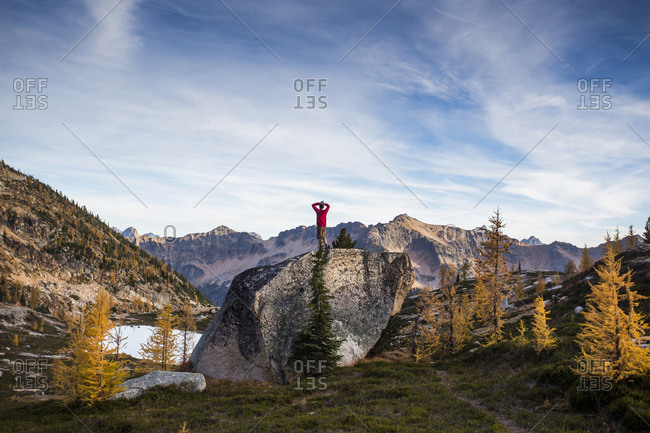 A climber stands on top of a rock alongside the colorful larch trees and steep mountains of the Cascades in the Pasayten Wilderness in Washington.