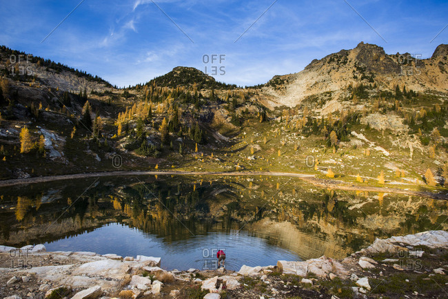 A young man walks next to an alpine lake beneath steep mountains of the Cascades in the Pasayten Wilderness in Washington.