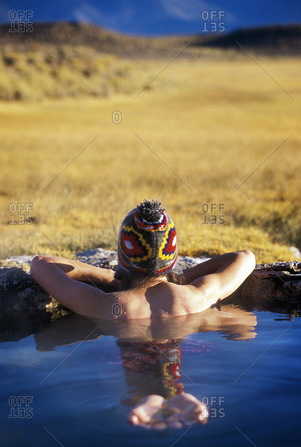 Lone woman sitting in hot spring in California.