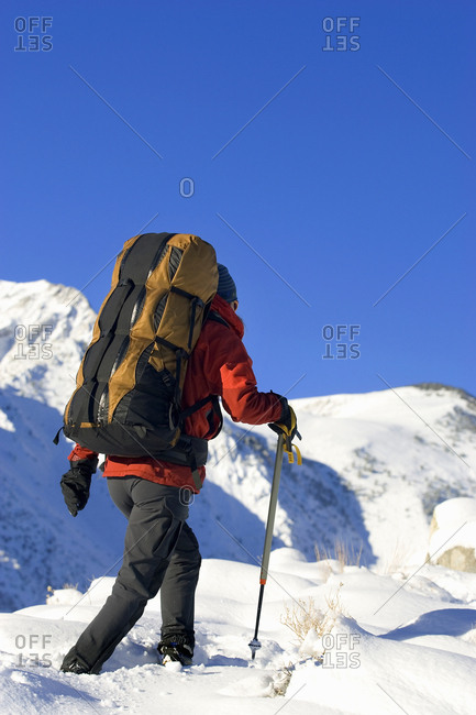 Woman carry large, heavy pack for winter camping. Sierra Nevada, California