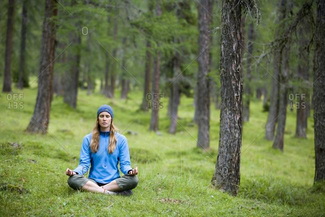 A woman meditates outdoors.
