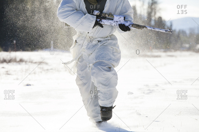 A hunter runs through a snow covered field while carrying his rifel.
