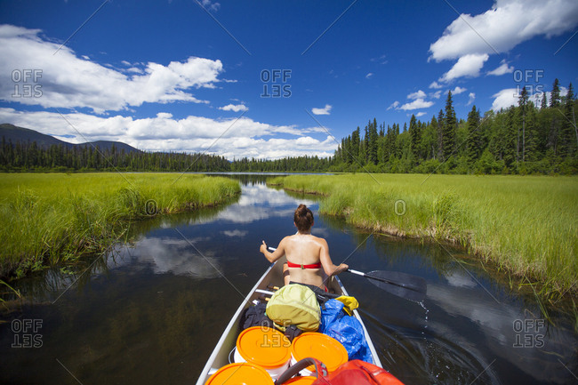 A young woman paddles through a narrow channel in Bowron Lake Provincial Park