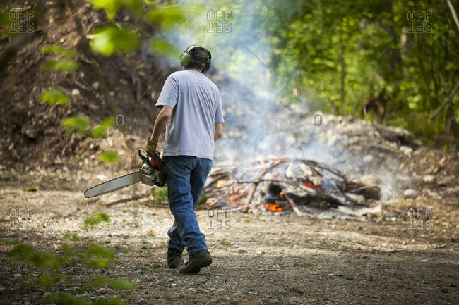 A middle aged man uses a chainsaw while cleaning up his yard.