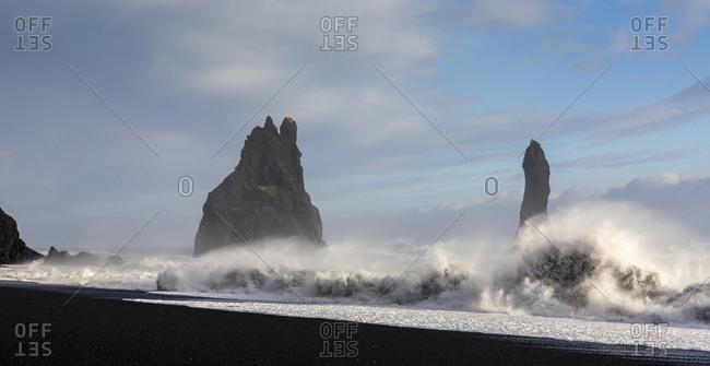 Waves crashing onto the beach and basalt columns