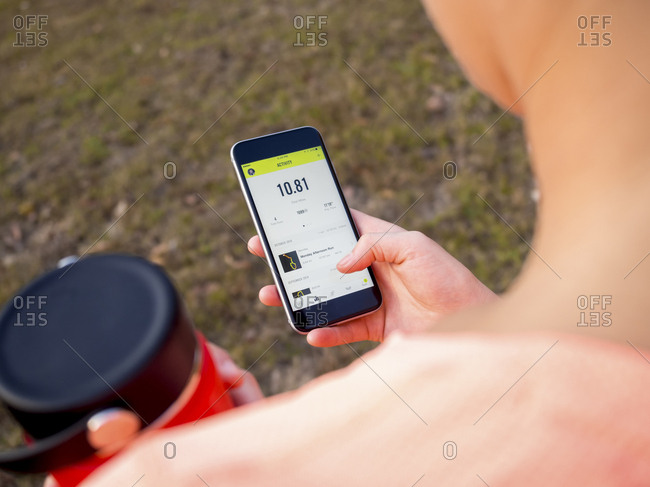 A Young Woman Holding A Water Bottle Checks A Running App On Her Phone After A Trail Run During The Fall