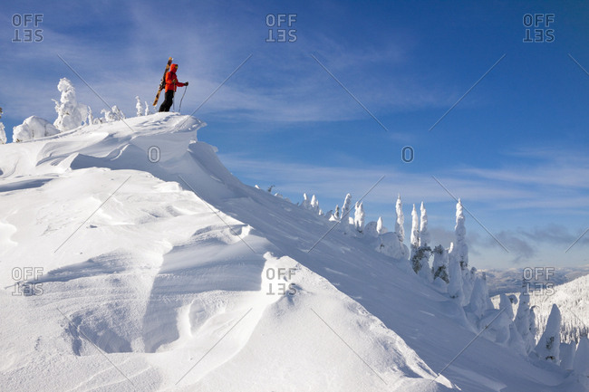 A Male Skier Standing On The Summit Of Snowy Mountain In Whitefish, Montana, USA