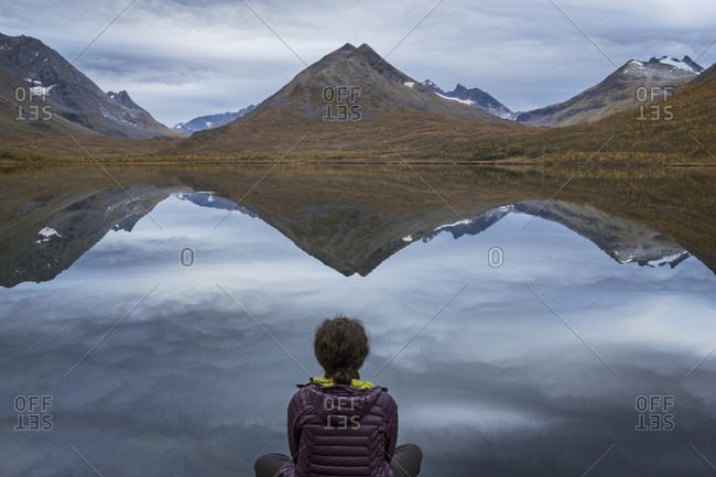 Woman sitting on shore of Lake Nakkevatnet, Troms County, Norway