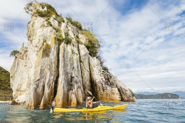 Woman kayaking beside Abel Tasman National Park cliffs