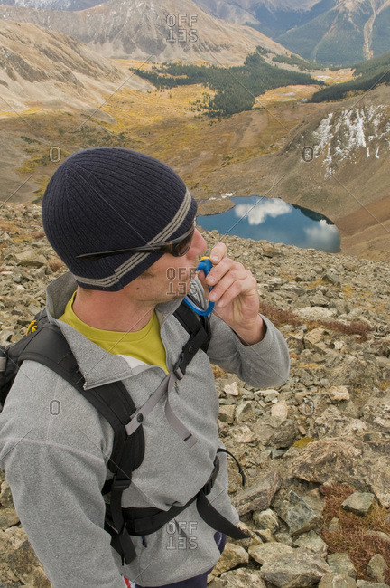 A man stops to hydrate while hiking along an alpine ridge on a crisp fall day.
