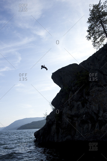 A young man flips off a rock outcropping in Idaho.