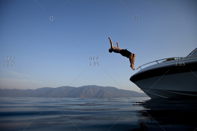 Young man flips off a boat at sunset in Idaho.