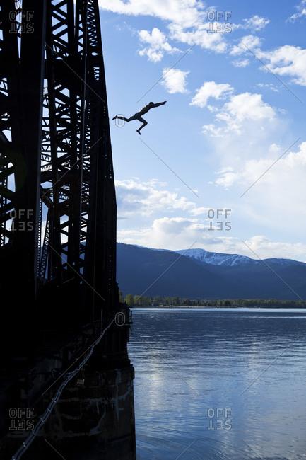 A athletic man jumps off a train bridge in Idaho.