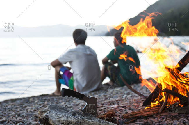 Two young men sit next to a campfire next to a lake on a camping trip in Idaho.