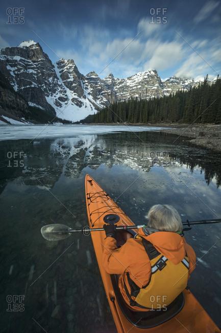 Man kayaking in Moraine Lake in winter, Banff National Park, Alberta, Canada