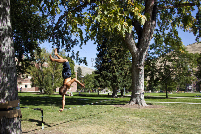 A professional slackliner plays around on the slackline on a university campus