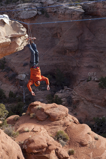 A highliner takes a fall with a rope tied to both feet, Moab Utah.