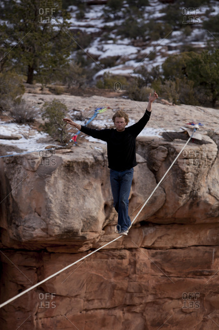A man crossing a highline with no leash and breaking the world record as he becomes the first person to free solo a highline one hundred and thirty feet long, Moab, Utah.