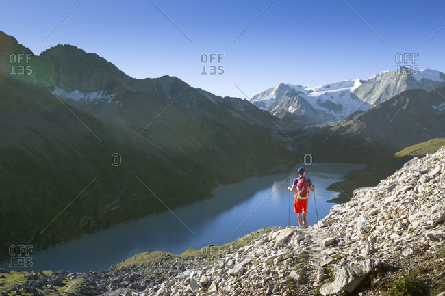 A solo male hiker enjoying the view over Lac des Dix in Val in the Swiss Alps.