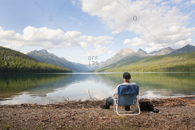 An older man sits next to a lake in Glacier National Park, MT