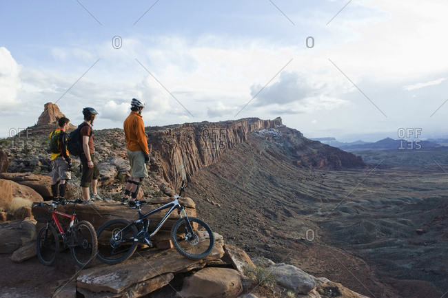 Three young men overlook a canyon after biking up the Amasa Back Trail, Moab, UT.