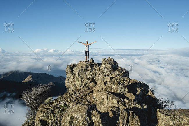 Woman stands on a mountain top over the clouds on a blue sky morning