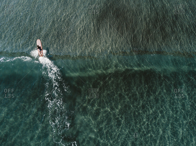 Aerial view of female surfer surfing in crystal clear water, Tenerife, Canary Islands, Spain