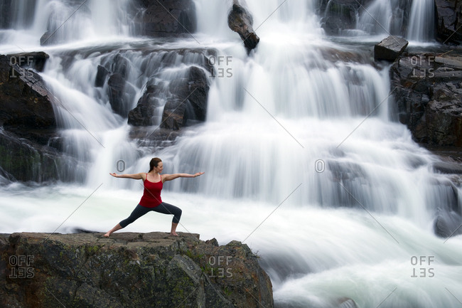 A woman performs yoga in front of a large waterfall in Lake Tahoe, California.