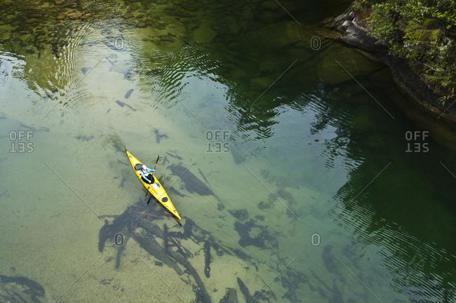 Woman paddling a sea kayak,  Abel Tasman National Park, Nelson, New Zealand.