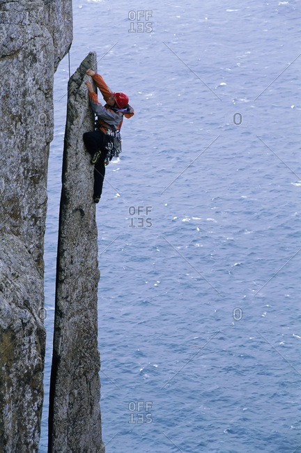 A woman rock climbs a steep face on a sea cliff.
