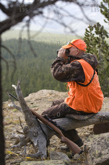 A rifle hunter sits on a log while glassing a distant forest with binoculars.