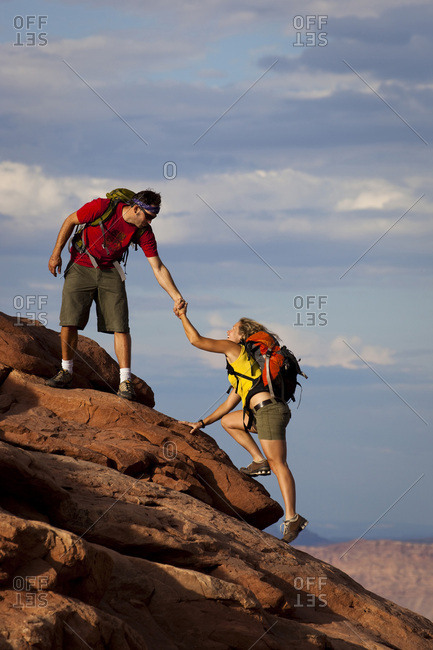 A man reaching down and helping a woman up a rock step in Arches National Park, Utah.