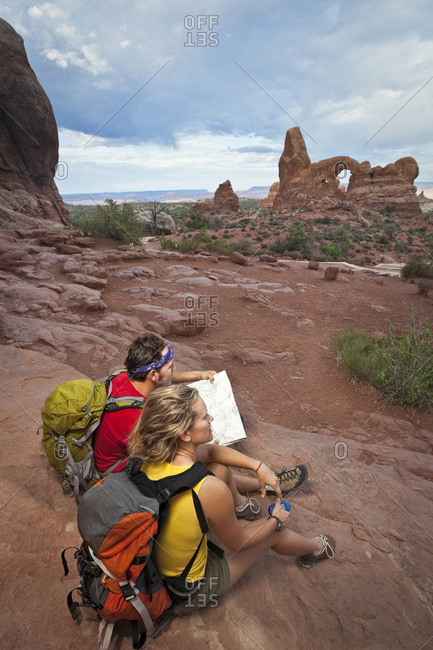 A couple looking out into the distance while holding a map and GPS in Arches National Park, Utah.