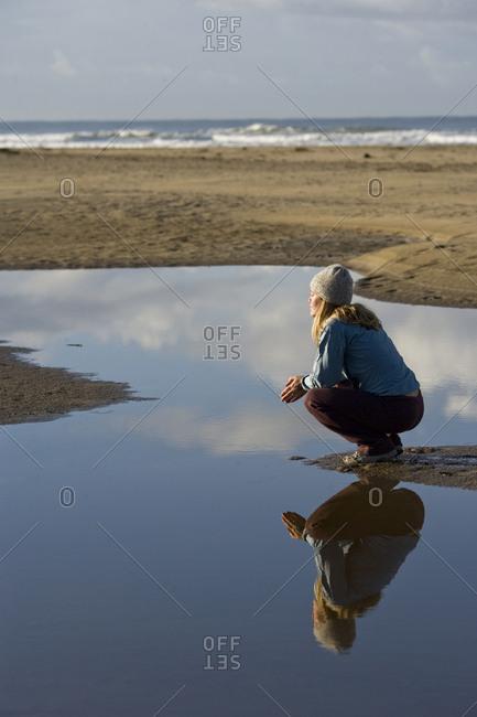Woman sitting quietly near tidal pond on beach