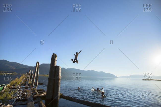 Group of friends swimming and jumping into water in Lake Pend Oreille