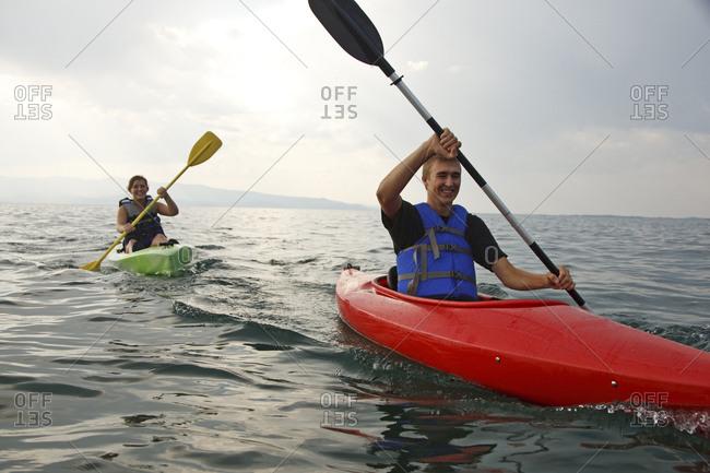 A teenage boy and girl smile as they paddle their colorful kayaks across Flathead Lake, Montana.