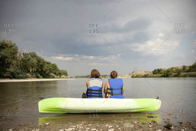 Two girls in blue life jackets sit on a green kayak after a day of kayaking the Yellowstone River in Eastern Montana.