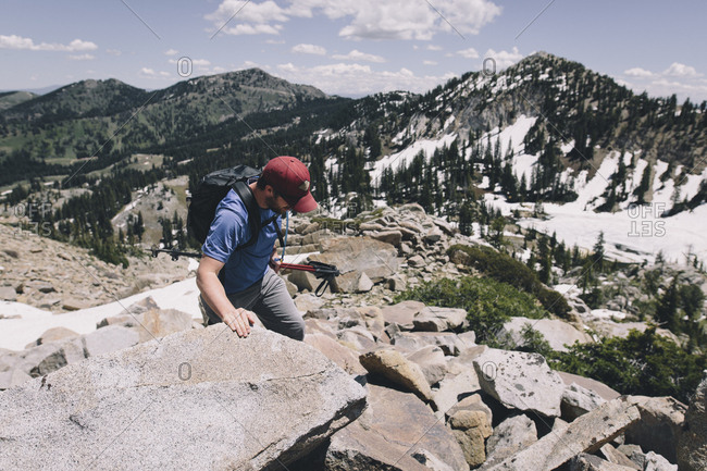 A man scrambles over boulders in Utah's Big Cottonwood Canyon, Utah.