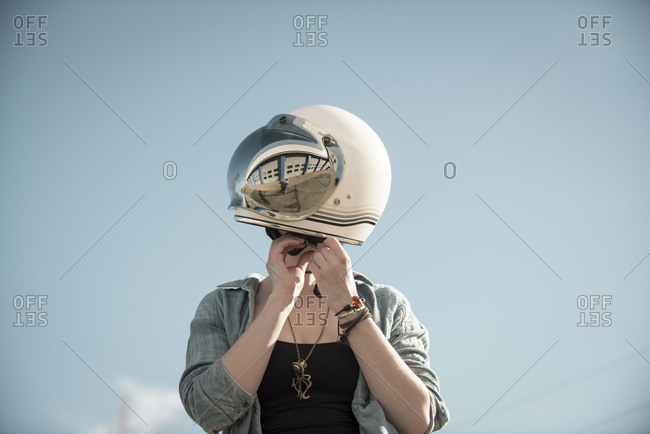 Woman standing adjusting her vintage motorcycle helmet with a reflection of a auto garage.