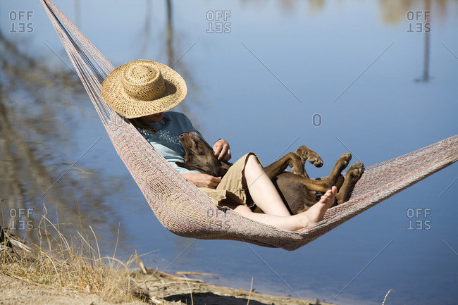 Young woman in a hat resting in hammock with her dog in Bishop, CA.
