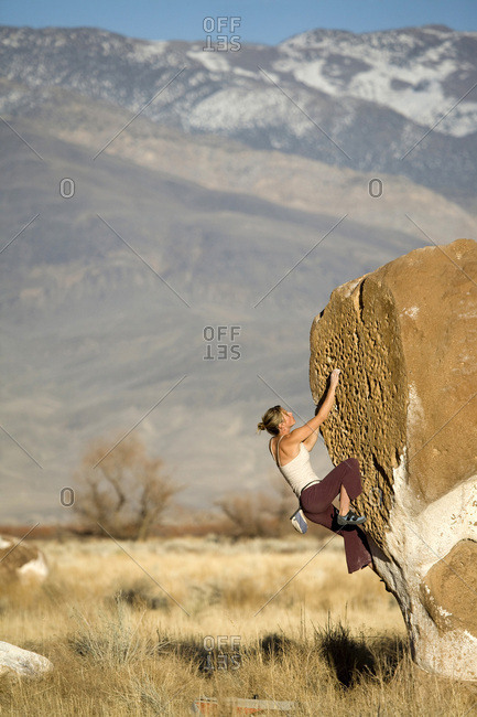 Young woman bouldering in Bishop, CA.
